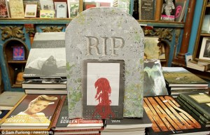 """Display of books with a tombstone and a """"bleeding"""" Kindle"""